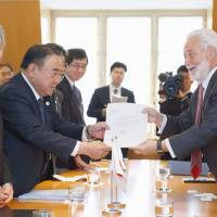 In the running: Japanese Ambassador to France Masato Kitera (second left) hands an application to BIE Secretary General Vincente G. Loscertales. | KYODO