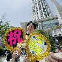 Five years old: A visitor celebrates Tokyo Skytree's fifth anniversary in front of the tower in Sumida Ward. | KYODO