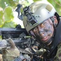 A member of the Japan Ground Self-Defense Force takes part in an amphibious drill on May 13 during joint military exercises on Guam involving Japan, the U.S., France and Britain that were intended to show support for the free passage of vessels in international waters amid concerns China may restrict access to the South China Sea. | AP