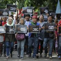 Filipino activists shout slogans as they march toward Camp Aguinaldo military headquarters in Manila during a Monday rally to oppose the declaration of martial law in Mindanao. | AP