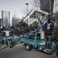 A employee for Bluegogo, a bike-sharing company, unloads bikes in Beijing on March 14. China's sharing-economy sector conducted business worth $500 billion last year. | BLOOMBERG