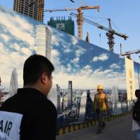 People walk past a construction site in the central business district of Beijing on May 18. Public works spending in China continues to focus on construction and the country has remained the world's top builder of skyscrapers for nine years in a row. | AFP-JIJI