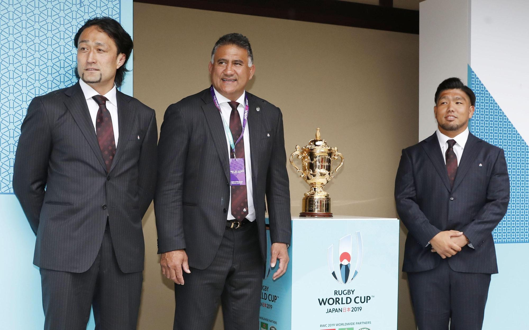 Brave Blossoms head coach Jamie Joseph (center) and players Hitoshi Ono (left) and Shota Horie pose with the Webb Ellis Cup during the Rugby World Cup draw on Wednesday in Kyoto. | KYODO