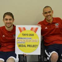 Jeff Butler (left) and Ernie Chun of the United States donate old mobile phones to the Tokyo 2020 Medal Project on Saturday. The project aims to collect materials to be recycled and used in the manufacturing of medals for the Tokyo 2020 Olympics and Paralympics. | JAPANESE PARA-SPORTS ASSOCIATION
