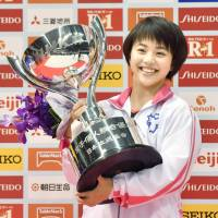 Mai Murakami holds the trophy after winning the all-around title at the NHK Cup Saturday. | KYODO