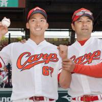 Carp pitcher Yuta Nakamura (left) and manager Koichi Ogata pose for photos after Hiroshima's win over the Dragons on Wednesday. | KYODO