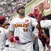 Rakuten's Carlos Peguero is congratulated by his teammates after hitting a grand slam against Seibu in the fourth inning on Saturday in Sendai. The Eagles won 6-1. | KYODO
