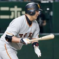 The Giants' Shinnosuke Abe strokes a two-run single in the fifth inning against the Swallows on Tuesday night at Tokyo Dome. Abe drove in four runs in the game. | KYODO