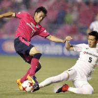 Cerezo Osaka's Ryuji Sawakami (left) tries to control the ball while being challenged by Vissel Kobe's Takuya Iwanami during their Levain Cup match on Wednesday. Cerezo won 1-0. | KYODO