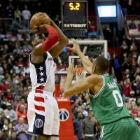 Wizards guard John Wall shoots a 3-pointer over the Celtics' Avery Bradley during the final seconds of his team's 92-91 victory on Friday in Washington. The Wizards tied the series 3-3. | USA TODAY / VIA REUTERS