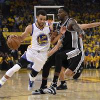 Golden State's Stephen Curry (left) dribbles against San Antonio's Dewayne Dedmon during the Warriors' 136-100 win in Game 2 of the Western Conference finals in Oakland, California, on Tuesday. | USA TODAY / VIA REUTERS