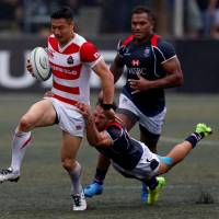 The Brave Blossoms' Naoki Ozawa is tackled by Hong Kong's Phil Whitfield during the Asia Rugby Championship on Saturday in Hong Kong. Japan defeated Hong Kong 16-0 to defend its title. | REUTERS