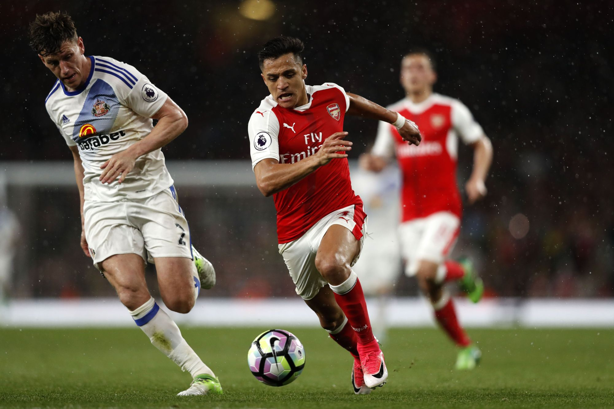 Arsenal's Alexis Sanchez (right) takes on Sunderland's Billy Jones during their Premier League match in London on Tuesday.   AFP-JIJI