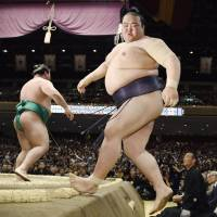 Kisenosato steps off the raised ring after losing to Yoshikaze on the opening day of the Summer Grand Sumo Tournament on Sunday. | KYODO