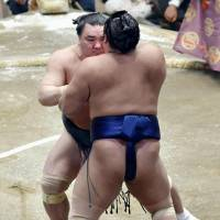 Harumafuji (rear) grapples with Tochiozan at the Summer Grand Sumo Tournament on Tuesday. Harumafuji won and improved to 10-0 at the 15-day meet. | KYODO