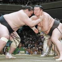 Yokozuna Hakuho (right) battles Terunofuji during their match on the 14th day of the Summer Grand Sumo Tournament on Saturday. Hakuho won to clinch the title with a day to spare. | KYODO