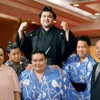 Takayasu (center) celebrates his promotion to sumo's second-highest rank of ozeki on Wednesday alongside his mother Bebelita (front left) and father Eiji (front right). | KYODO
