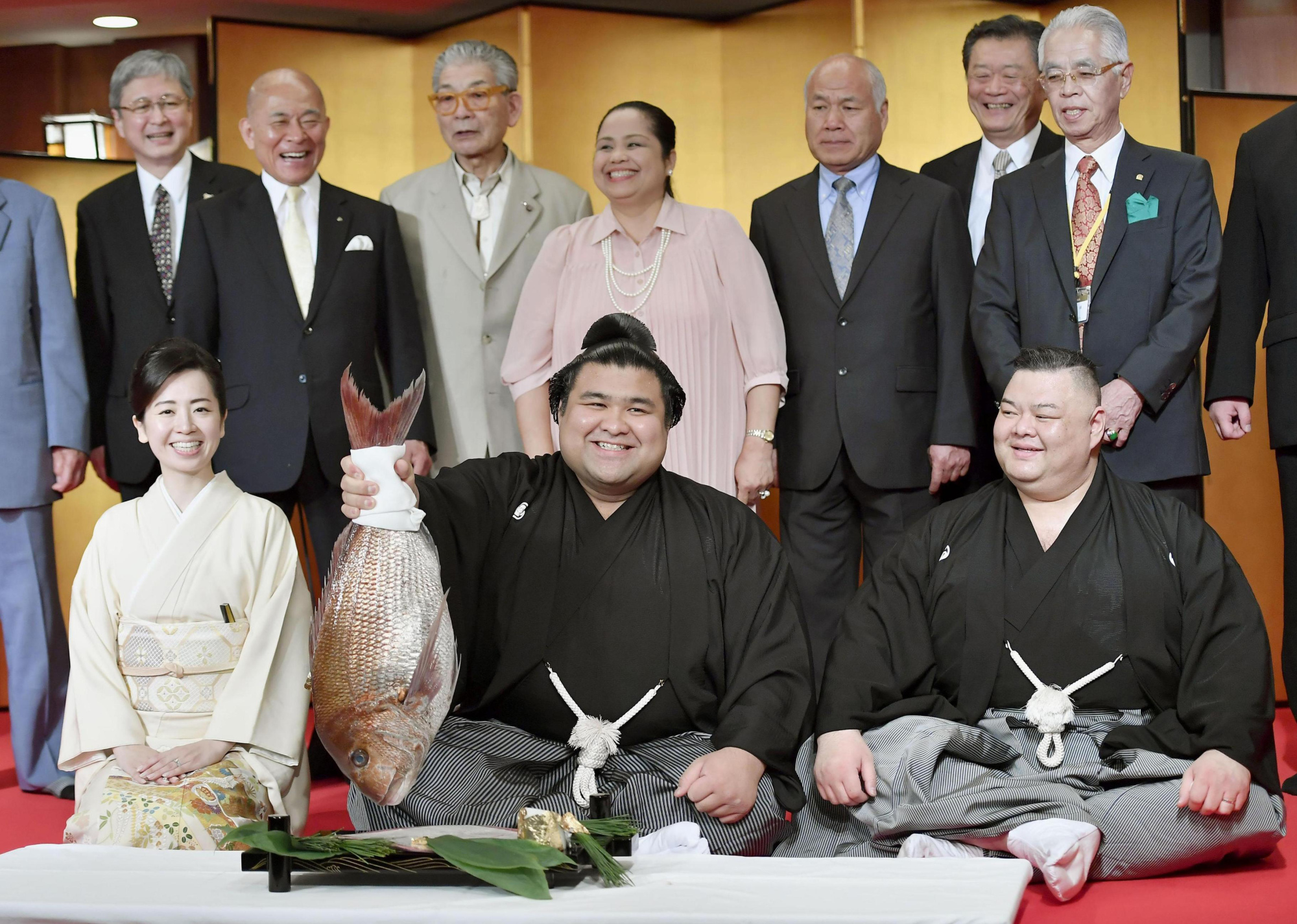 Takayasu, surrounded by friends and family including mother Bebelita (center, rear) and father Eiji (center right, rear), holds up a fish after being promoted to ozeki on Wednesday. | KYODO