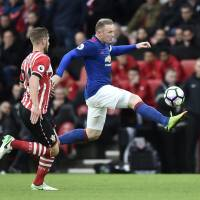 Manchester United's Wayne Rooney (right) controls the ball as Southampton's Jack Stephens looks on during Wednesday's Premier League match in Southampton, England. | REUTERS