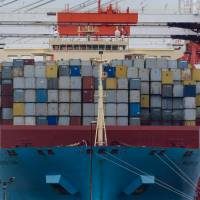 A container ship sits berthed at a shipping terminal in Yokohama. | BLOOMBERG