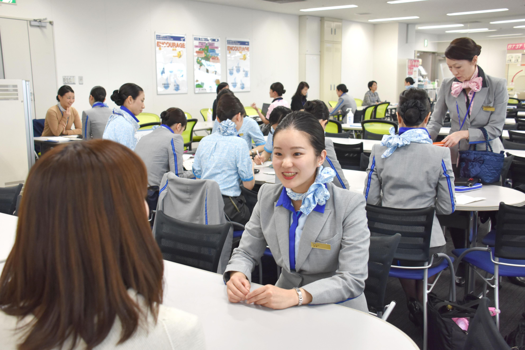 All Nippon Airways cabin attendant Risa Seike joins a staff meeting at Tokyo's Haneda airport after her in-flight duties. | KYODO