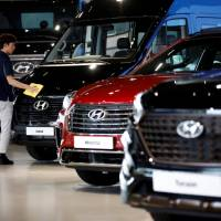 A staffer polishes Hyundai vehicles at a showroom in Goyang, South Korea, last month. | REUTERS