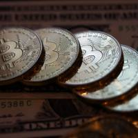 The euphoria over bitcoin reached a fever pitch last week, but its slow transaction times and inertia are helping to prevent widespread usage. | BLOOMBERG