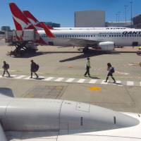 An official watches passengers as they walk along the tarmac to board a Qantas Airways Boeing 737-800 at Sydney's domestic airport terminal in October.   REUTERS