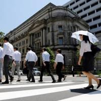 Office workers walk past the Bank of Japan building in Tokyo on Friday. | REUTERS