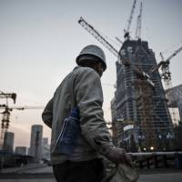 A worker walks past cranes operating on a construction site in Beijing. A Bloomberg analysis of International Monetary Fund data shows China's transformation from rags to riches isn't over quite yet. | BLOOMBERG