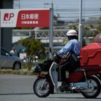 Japan Post Holdings Co. is among large Japanese companies that have seen massive write-downs from their overseas investment deals. | BLOOMBERG