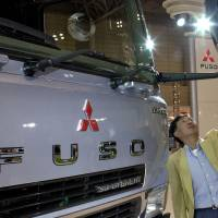 A man looks at a Mitsuibishi Fuso truck in a showroom. Mitsubishi Fuso Truck & Bus Corp. saw its sales in Indonesia jump by nearly a quarter in the first five months of 2017. | C. PERTWEE / BLOOMBERG NEWS