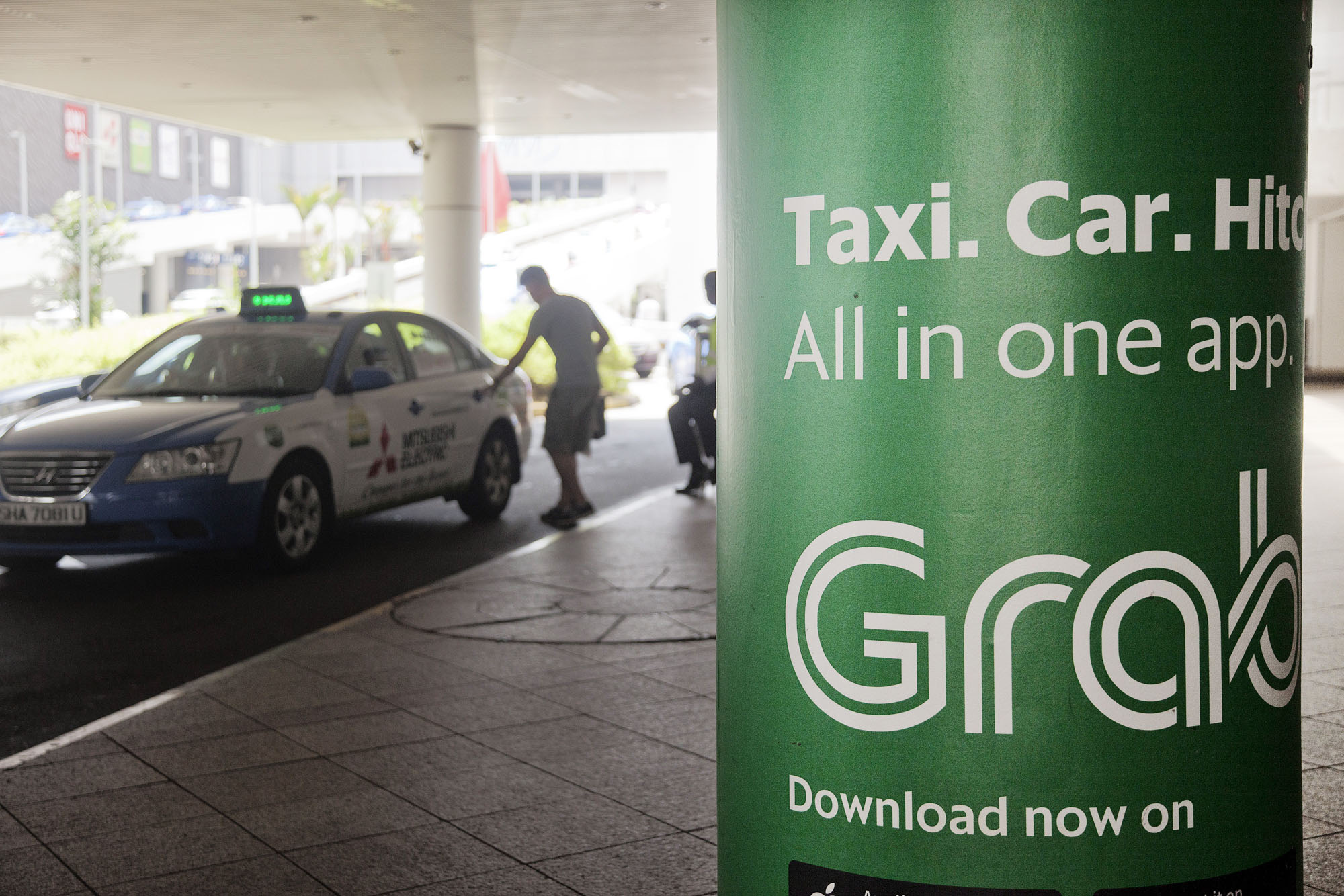An advertisement for Grab is seen at a taxi stand in Singapore. Grab is hunting for deals with funding from SoftBank, its biggest backer. | BLOOMBERG