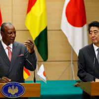 Guinea's President Alpha Conde and Prime Minister Shinzo Abe attend a joint news conference at the Prime Minister's Office in Tokyo on Tuesday. | REUTERS