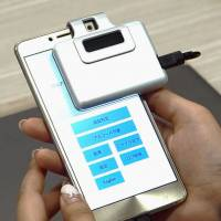 Hitachi Ltd.'s new alcohol detection device attaches to a smartphone. | KYODO