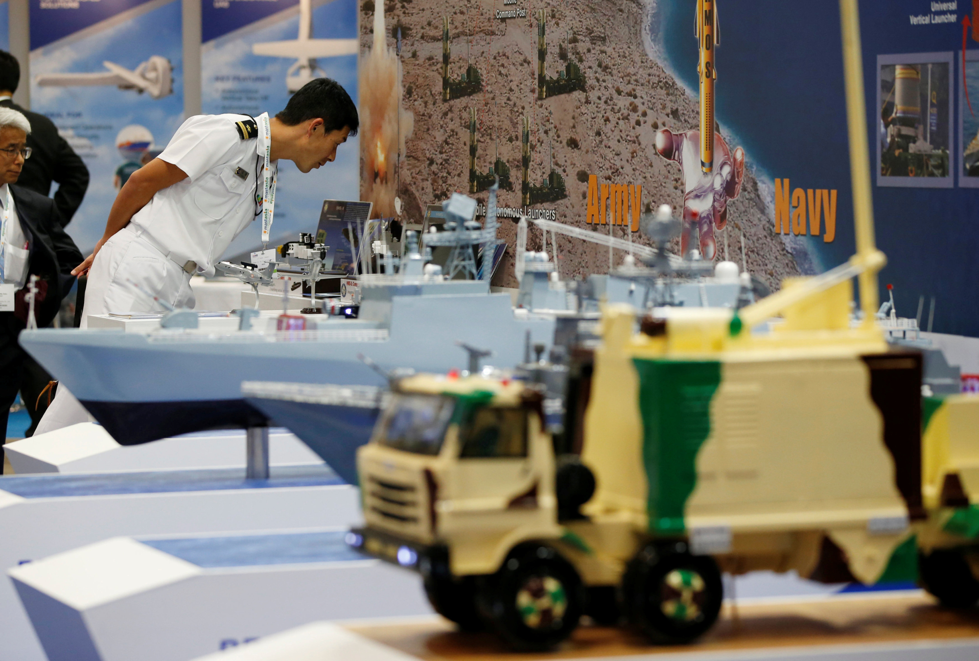Visitors look at miniature models of military equipment at the Maritime Air Systems and Technologies Asia (MAST) show in the city of Chiba Monday.   REUTERS