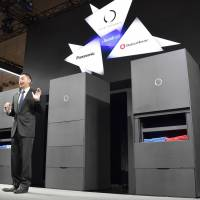 Seven Dreamers Laboratories Inc. President Shinichi Sakane shows off his firm's laundry-folding robot, which uses artificial intelligence, at an event last year. It has recently begun accepting orders for the machines priced at about ¥2 million per unit.   KYODO