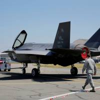 U.S. soldiers walk next to a Lockheed Martin F-35 Lightning II aircraft, as it is moved, on the eve of the 52nd Paris Air Show at Le Bourget Airport near Paris Sunday. | REUTERS