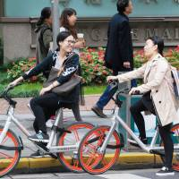 Women are seen riding bicycles provided by bike-sharing service Mobike in Shanghai last October. | KYODO