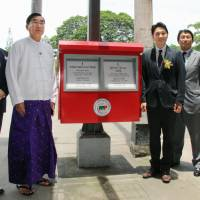 A new postbox is shown to the media in Yangon on Tuesday. Japan is offering assistance to help Myanmar reform its aging postal system. | KYODO