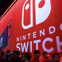 Attendees wait in line for the Nintendo Co. Switch video game console during the Electronic Entertainment Expo in Los Angeles on Tuesday. | BLOOMBERG