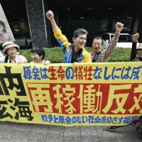 People protest the use of nuclear energy in front of a venue where Kyushu Electric Power holds its general shareholders' meeting Wednesday in Fukuoka. | KYODO