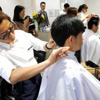A barber cuts hair at QB House's first outlet in New York on Thursday. | KYODO