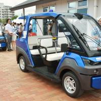 Self-driving vehicles are readied for a road test Monday in Chatan, Okinawa Prefecture.   KYODO