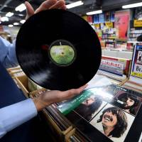 A shop manager shows off a period Japanese pressing of The Beatles' final studio album 'Let It Be' at the RECOfan music shop in Tokyo's Shibuya district on Thursday. Sony said it will start making vinyl records again on the back of surging demand for a technology that the Japanese firm abandoned three decades ago. | AFP-JIJI