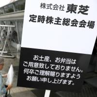 A sign guides Toshiba shareholders to their meeting Wednesday at the Makuhari Messe convention hall in the city of Chiba. The sign also offers an apology for not preparing souvenirs or bento lunch boxes this time. | KYODO