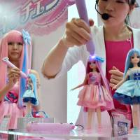 A Tomy Co. employee demonstrates how Kirachen Licca-chan changes its hair color by casting a special light with a pen-shaped tool, during the annual International Tokyo Toy Show that kicked off Thursday at Tokyo Big Sight in Koto Ward. | SATOKO KAWASAKI