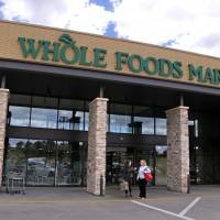 People stand outside a Whole Foods Market in Upper Saint Clair, Pennsylvania, in May. Amazon's planned $13.7 billion acquisition of Whole Foods signals a massive bet that people will opt more for the convenience of online orders and delivery or in-store pickup, putting even more pressure on the already highly competitive industry. | AP