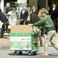 A Yamato Transport worker handles parcels in the Tokyo's Ginza district in March. KYODO