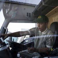 A Yamato Transport Co. driver checks his delivery truck before departing a Yamato branch in Musashimurayama, Tokyo, on Tuesday. | BLOOMBERG